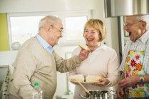 Rire amis aînés cuisine dans la cuisine — Photo de stock