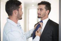 Небрежно одетый человек, регулируя галстук брат-близнец в офисе — стоковое фото