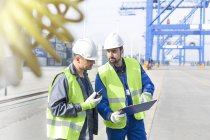 Two men with clipboard and walkie-talkie talking at container port — Stock Photo