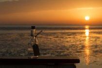 Allemagne, Basse-Saxe, Brême, Bouteille vide au coucher du soleil sur l'eau — Photo de stock