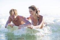 Glückliches junges Paar auf Surfbretter im Meer liegen — Stockfoto
