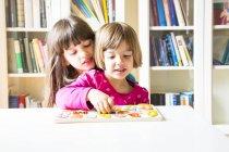 Due sorelle sedute con puzzle in alfabeto di legno — Foto stock
