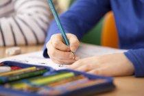 Ученики, работающие на рабочих листах в классе — стоковое фото