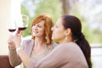 Две женщины изучают красное вино — стоковое фото
