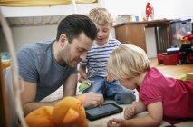 Батько і діти з допомогою планшета — стокове фото