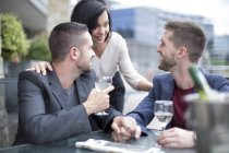 Gay couple sharing meal with a female friend and drinking wine — Stock Photo