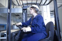 Female Worker in factory hall on forklift — Stock Photo