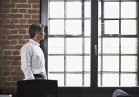 Businessman in office looking out of window — Stock Photo