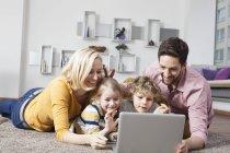 Familia feliz usando el ordenador portátil en casa - foto de stock