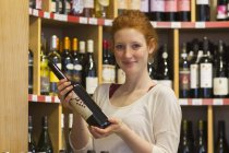 Portrait of smiling young woman in wholefood shop holding wine bottle — Stock Photo