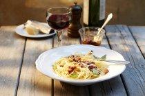 Piatto di spaghetti con pesto di pomodoro e parmigiano grattugiato e bicchiere di vino rosso — Foto stock