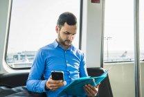 Joven empresario sentado en autobús con smartphone en el aeropuerto - foto de stock
