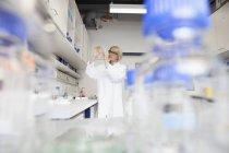Scientifique avec boîte de Pétri en laboratoire — Photo de stock