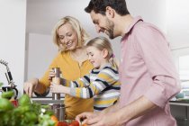 Mother, father and daughter cooking in kitchen — Stock Photo