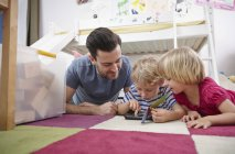 Father and children using mini tablet — Stock Photo