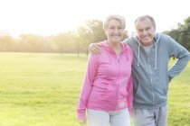 Portrait of happy senior couple wearing sports wear standing in a park — Stock Photo