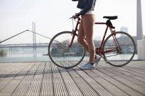 Femme avec vélo debout en face du Rhin — Photo de stock