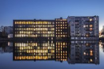 Germany, Berlin, lighted office building and water reflections in the evening — Stock Photo