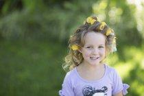 Lächelnde Blumenmädchen mit Lockenwicklern im Haar — Stockfoto