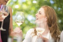 Woman examining white wine on a wine tasting session — Stock Photo