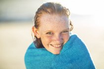 Portrait of smiling girl on the beach wrapped in a beach towel — Stock Photo