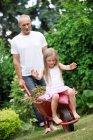 Man pushing his little daughter sitting in a wheelbarrow — Stock Photo