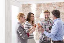 Happy business people toasting with champagne glasses in modern office — Stock Photo