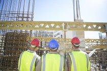 Trois travailleurs de la construction en chantier — Photo de stock