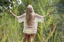 Teenage girl in garden, wearin yellow bikini — Stock Photo