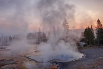 USA, Wyoming, Yellowstone National Park, steam rising up from Firehole Spring at sunrise — Stock Photo