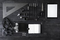 Camera, note book, digital tablet and tools on black wood — Stock Photo