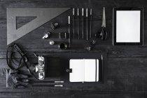 Камера, записная книжка, цифровой планшет и инструменты на черном дереве — стоковое фото
