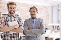Retrato de dois empresários confiantes em pé no escritório moderno — Fotografia de Stock