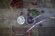 Glas mit Kirschmarmelade und frischen Kirschen auf dunklem Holz — Stockfoto