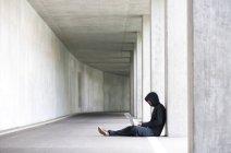 Hacker mit Laptop sitzen in einer Tiefgarage — Stockfoto