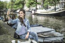 Turista Holanda, Amsterdam, teniendo un descanso tomando un selfie frente canal ciudad - foto de stock