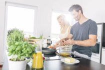 Couple preparing scrambled eggs together in the kitchen — Stock Photo