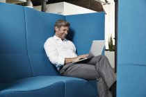 Smiling businessman sitting in conversation pit in office using laptop — Stock Photo