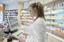 Young pharmacist working in pharmacy — Stock Photo