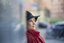 Portrait of smiling young woman wearing black hat and red scarf — Stock Photo