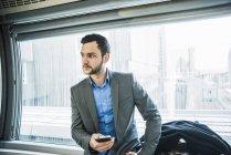 Joven empresario con la situación del teléfono celular en metro - foto de stock