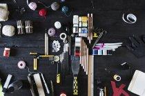 Disposición de materiales de arte y herramientas en madera negra - foto de stock