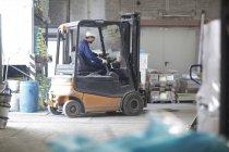 Homem na empilhadeira no hall de fábrica — Fotografia de Stock