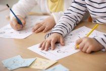 Écolières travaillant sur des feuilles de travail en salle de classe — Photo de stock