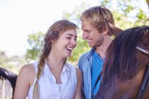Feliz pareja joven con caballo - foto de stock