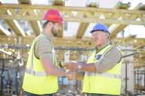 Два строителя пожимают руки на стройке — стоковое фото