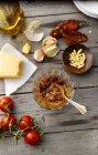 Recipiente de vidrio de pesto de tomate y los ingredientes en la madera gris - foto de stock