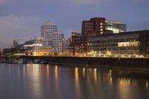 Germany, Duesseldorf, media harbor at dusk against water — Stock Photo