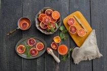 Tranches d'oranges sanguines et verre de jus d'orange sanguine sur bois foncé — Photo de stock