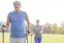 Senior couple doing Nordic Walking in a park — Stock Photo